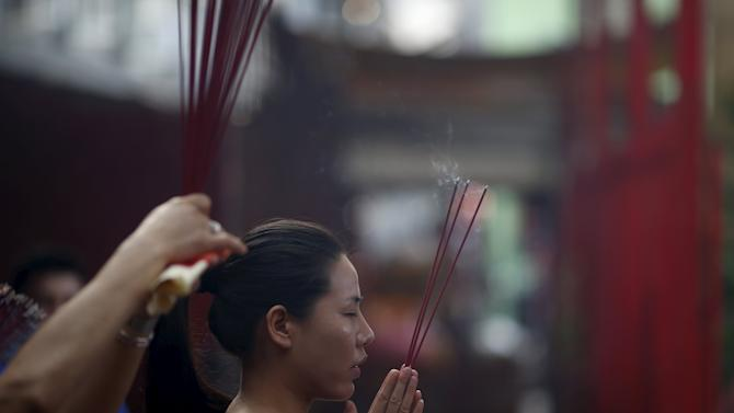 A woman prays with joss sticks at Dharma Bhakti Temple on the first day of the  Lunar New Year in Jakarta, Indonesia