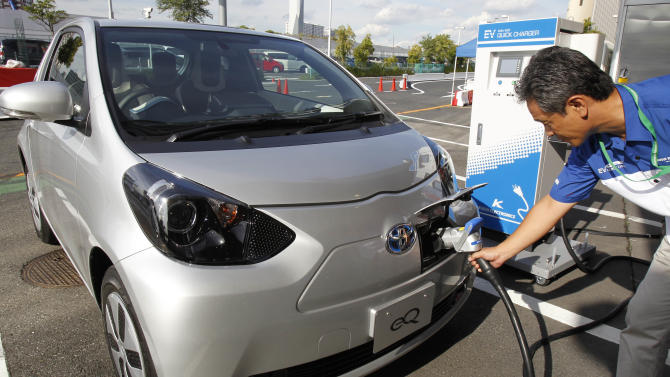 "A participant to a press event by Toyota Motor Corp. puts a quick charger plug into the newly-developed compact electric vehicle ""eQ"" during a test drive at a press event in Tokyo Monday, Sept. 24, 2012. Toyota is boosting its green vehicle lineup, with plans for 21 new hybrids in the next three years, a new electric car later this year and a fuel cell vehicle by 2015 in response to growing demand for fuel efficient and environmentally friendly driving. (AP Photo/Koji Sasahara)"