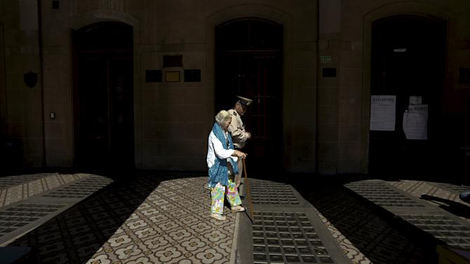 A member of Argentina's coast guard assists a woman arriving at a polling station at a primary election in Buenos Aires