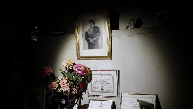 """In this Nov. 26, 2012 photo, a 1940's portrait of journalist and radio host Maria Julia Venegas, university titles and certificates are on display at her home in Lima, Peru. Venegas who began broadcasting """"Radio Club Infantil,"""" a show for Peru's children in the golden age of radio and World War II, has earned a citation from Guinness World Records as the globe's longest-running radio personality. (AP Photo/Karel Navarro)"""