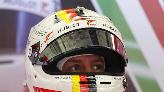 Ferrari Formula One Driver Vettel of Germany wears his helmet at the pit-lane during the third free practice ahead of Bahrain's F1 Grand Prix