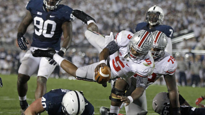 Ohio State quarterback Braxton Miller (5) dives over Penn State linebacker Glenn Carson (40) for a third-quarter touchdown during an NCAA college football game in State College, Pa., Saturday, Oct. 27, 2012. (AP Photo/Gene J. Puskar)