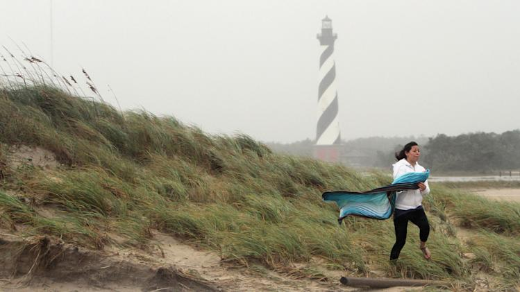 Teresa Perez of Buxton, N.C., runs off a sand dune near Cape Hatteras Lighthouse on Hatteras Island Sunday, Oct. 28, 2012, as Hurricane Sandy works its way north, battering the U.S. East Coast. (AP Photo/The Virginian-Pilot, Steve Earley)