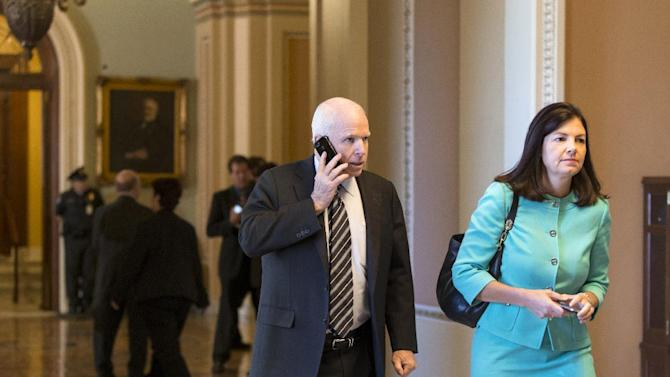 Sen. John McCain, R-Ariz., left, and Sen. Kelly Ayotte, R-N.H. walk to their party caucuses on Capitol Hill in Washington, Tuesday, Sept. 24, 2013, as the Senate struggles with a stopgap spending bill that would prevent a partial government shutdown when the budget year ends next week. Tea party-leaning members of the House GOP caucus successfully attached language to that bill last week that would strip funding for President Barack Obama's health care program. (AP Photo/J. Scott Applewhite)