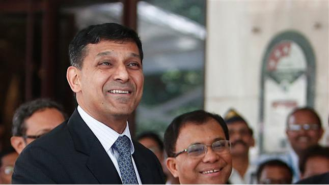 Newly appointed governor of RBI Rajan gestures while posing for photographers after his arrival at the bank's headquarters in Mumbai