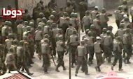 An image from a video on YouTube shows Syrian troops deploying in the Syrian city of Duma on Monday. Twin blasts targeting security buildings killed more than 20 people in the northwest Syrian city of Idlib, a monitoring group said, as the chief UN monitor presses both sides to end more than 13 months of violence