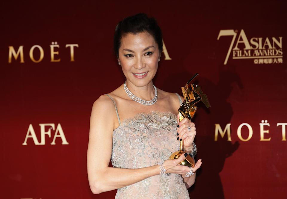 Malaysia actress Michelle Yeoh poses with her trophy after winning the Excellence in Asian Cinema Award at the Asian Film Awards as part of the 37th Hong Kong International Film Festival in Hong Kong Monday, March. 18, 2013.  (AP Photo/Kin Cheung)