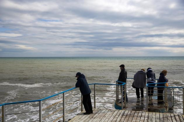People look out to the Black Sea at the embankment in the resort town of Alushta
