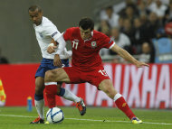 England's Ashley Cole, left, tackles Wales' Gareth Bale during their Euro 2012 Group G qualifying soccer match at Wembley Stadium, London, Tuesday, Sept. 6, 2011. (AP Photo/ Sang Tan)