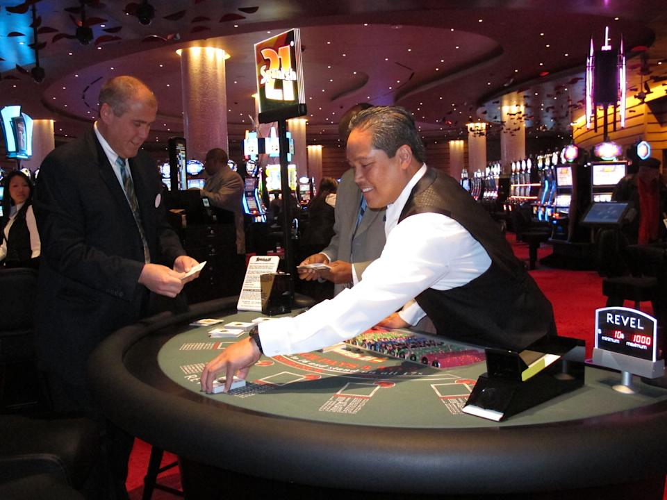 Dealer Elbert Taclan, right, prepares a card game moments after the $2.4 billion Revel casino resort opened in Atlantic City, N.J., Monday, April 2, 2012. John Koryto, left, was watching him prepare for the first customers to arrive at the table. (AP Photo/Wayne Parry)