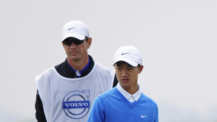 12-year-old Chinese amateur golfer Ye Wocheng, right, with his caddy watch his putt on the second day of the Volvo China Open at the Tianjin Binhai Lake Golf Club in north China's Tianjin Municipality Friday, May 3, 2013. Ye became the youngest player ever to compete in a European Tour event. (AP Photo) CHINA OUT