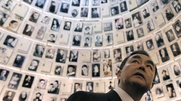Chinese Foreign Minister Wang Yi looks at pictures of Jews killed in the Holocaust during a visit to Yad Vashem in Jerusalem