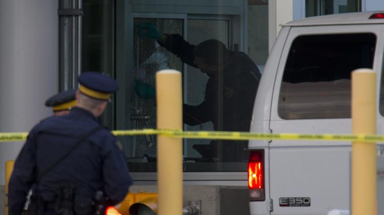 Police investigate a shooting at the Blaine, Wash./Surrey, British Columbia border crossing, Tuesday, Oct. 16, 2012, in Surrey. Royal Canadian Mounted Police Cpl. Bert Paquet says a border officer was in her booth when she was shot in the neck at about 2 p.m. Tuesday by a man trying to enter Canada in a van with Washington state plates. (AP Photo/The Canadian Press, Jonathan Hayward)