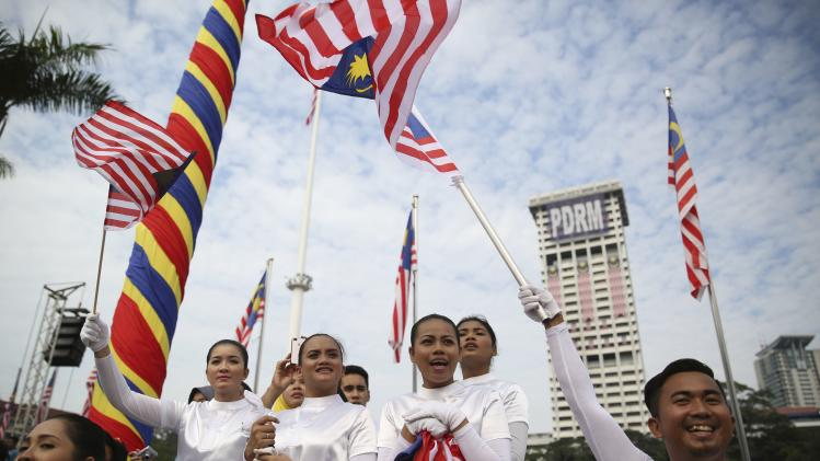 People cheer and wave national flags during Independence Day, or Merdeka Day, celebrations in Kuala Lumpur