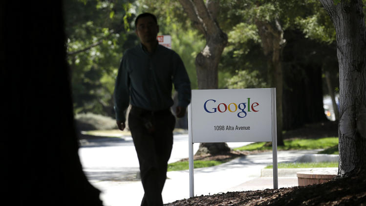 A man walks past a Google sign in Mountain View, Calif., Friday, June 7, 2013. Google CEO Larry Page is denying reports linking the Internet search company to a secret government program that has provided the National Security Agency access to email and other personal information transmitted on various online services. (AP Photo/Jeff Chiu)