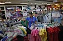 Sales assistant arranges clothing inside a V-Mart retail store in New Delhi