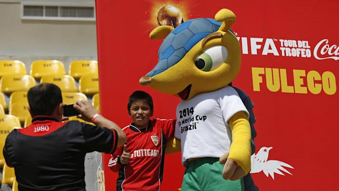 Soccer fans pose for a photo with Fuleco, the official mascot of the 2014 World Cup, at the El Campin stadium in Bogota, Colombia, Wednesday, Jan. 29, 2014. The FIFA 2014 World Cup trophy is on display in Bogota, as part of its world tour before the start of the World Cup in Brazil in June