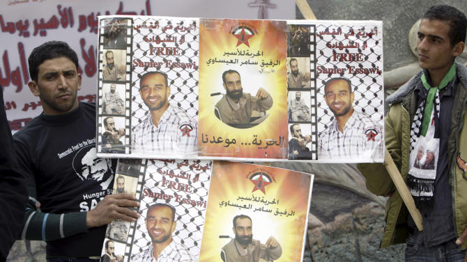 """In this Wednesday, April 17, 2013 file photo, Palestinians hold posters showing Samer Issawi during a rally calling for the release of Palestinian prisoners from Israeli jails in the West Bank city of Jenin. Arabic reads: """"free prisoner Samer Issawi"""". Lawyer Jawad Bulous says military prosecutors agreed early Tuesday to release Samer Issawi after he serves another eight months in prison. Bulous says the deal will be signed later in the day after which Issawi will end his hunger strike. (AP Photo/Mohammed Ballas, File)"""
