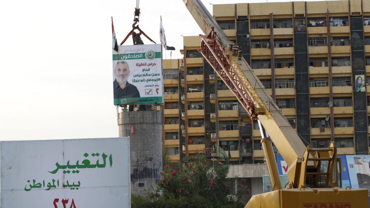 Workers use a crane to place an electoral campaign poster at al-Firdous square, where the statue of Saddam Hussein once stood, in central Baghdad
