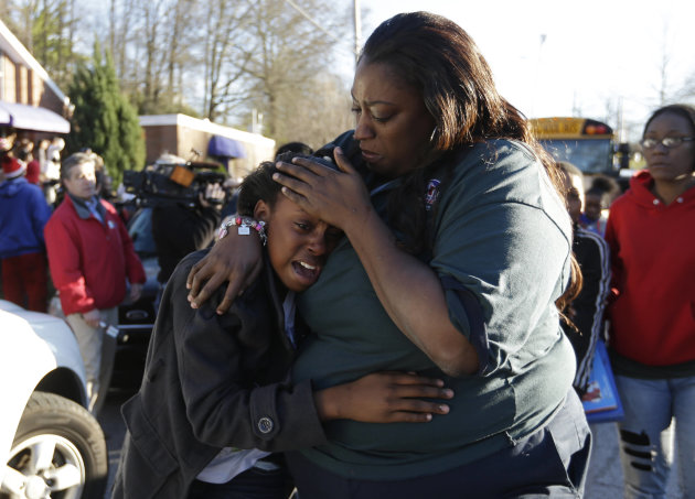 A woman comforts a child after after a shooting at an Price Middle school in Atlanta on Thursday, Jan. 31, 2013. A 14-year-old boy was wounded outside the school Thursday afternoon and a fellow studen