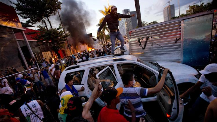 Protesters destroy a car from a car dealership during a demonstration in Belo Horizonte, Brazil, Wednesday, June 26, 2013. Brazilian anti-government protesters in part angered by the billions spent in World Cup preparations and police clashed Wednesday near the stadium hosting a Confederations Cup football match, with tens of thousands of demonstrators trying to march on the site confronting police firing tear gas and rubber bullets.(AP Photo/Victor R. Caivano)
