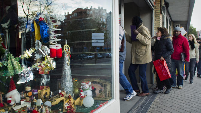 Christmas decorations are displayed in a store as people queue outside an unemployment registry office in Madrid on Thursday, Dec. 2, 2010. The number of people filing claims for unemployment benefits rose for a fourth consecutive month in November by 24,318 for a rounded total of 4.1 million people receiving payments. (AP Photo/Victor R. Caivano)