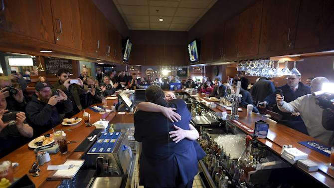 U.S. Republican presidential candidate and New Jersey Governor Chris Christie hugs bartender Angela Normyle as he makes a stop to greet voters at T-Bones Great American Eatery in Derry