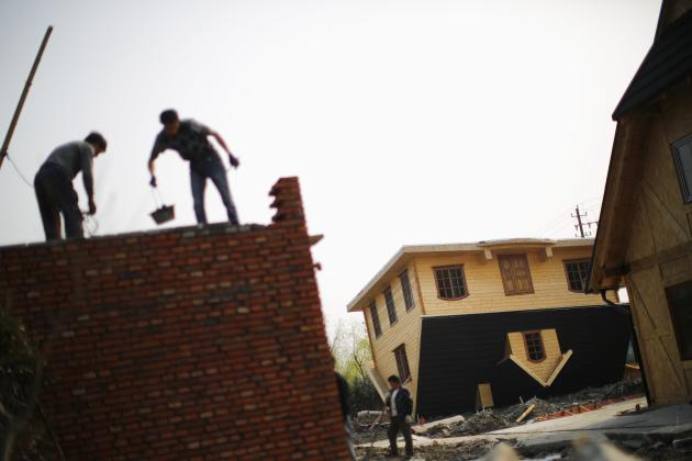 Labourers work at an upside-down house under construction at Fengjing Ancient Town, Jinshan District, South of Shanghai