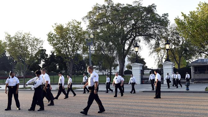 Uniformed Secret Service officers walk along Pennsylvania Avenue in front of the White House and head to Lafayette Park in Washington, Saturday, Sept. 20, 2014.   The Secret Service is coming under intense scrutiny after a man who hopped the White House fence made it all the way through the front door before being apprehended.  (AP Photo/Susan Walsh)