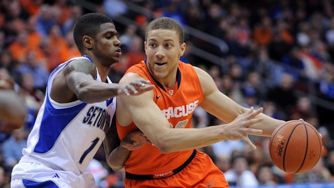 Syracuse's Brandon Triche, right, makes a move to get by Seton Hall's Aaron Cosby during the first half of an NCAA college basketball game Saturday, Feb. 16, 2013, in Newark, N.J. Triche led all scorers with a career-high 29 points as Syracuse defeated Seton Hall 76-65. (AP Photo/Bill Kostroun)