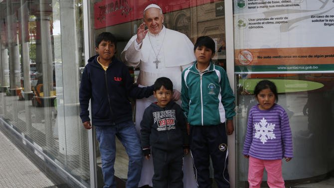 Boys pose for a pictures with a life-size cutout poster of Pope Francis, several days before of his arrival to Santa Cruz, Bolivia, Sunday, July 5, 2015. Francis is making his first visit as pope to his Spanish-speaking neighborhood. He'll travel to three South American nations, Ecuador, Bolivia and Paraguay, which are beset by problems that concern him deeply, income inequality and environmental degradation. (AP Photo/Juan Karita)