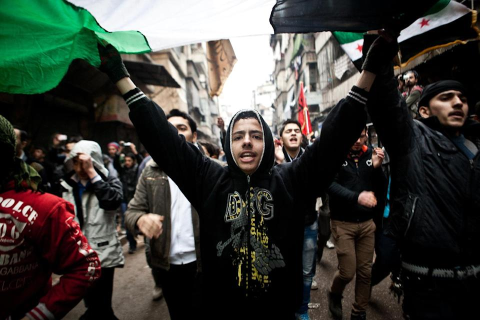 Syrians carry a large revolution flag and chant slogans during a Friday protest in Aleppo, Syria, where young people and children sang songs against Bashar Assad and the Syrian regime, Friday, Dec. 21, 2012.(AP Photo/Virginie Nguyen Hoang)