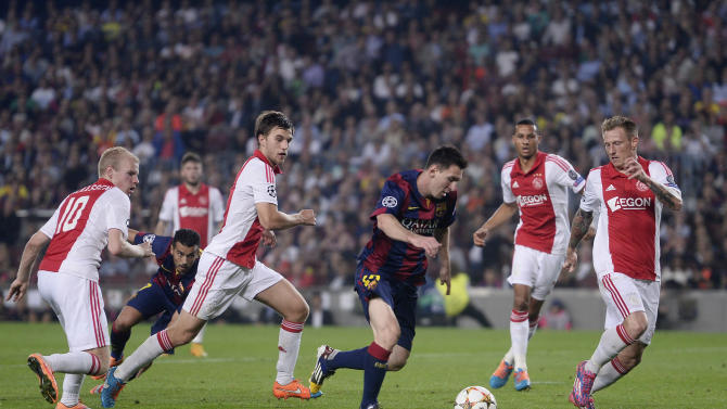 Barcelona's Lionel Messi, centre, prepares to shoot during the Champions League group F soccer match between F.C. Barcelona and Ajax at the Camp Nou stadium in Barcelona, Spain, Tuesday, Oct. 21, 2014. (AP Photo/Manu Fernandez)