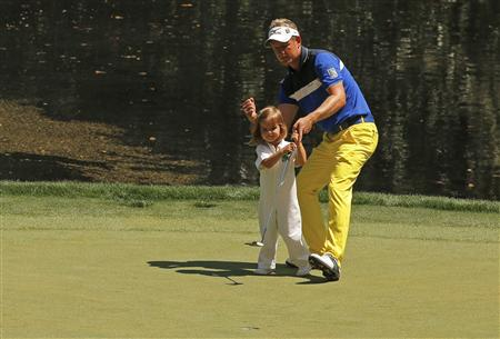 Britain's Donald reacts after his daughter Ellie holed a putt on the 9th green during the annual Masters Par 3 Contest at the Augusta National Golf Club in Augusta