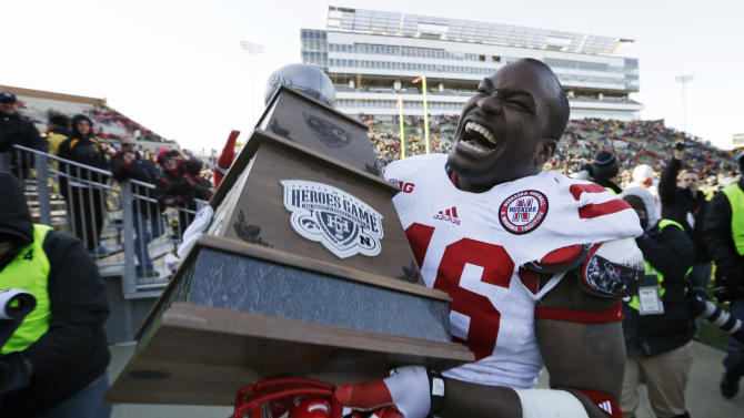 Nebraska linebacker Alonzo Whaley carries off the Heroes Game trophy after they defeated Iowa 13-7 in an NCAA college football game, Friday, Nov. 23, 2012, in Iowa City, Iowa. (AP Photo/Charlie Neibergall)