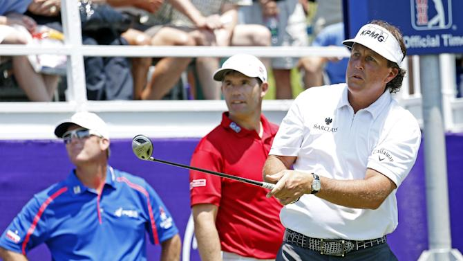D.A. Points, left, Padraig Harrington, center, watch as Phil Mickelson hits his drive on the first tee during the second round of the St. Jude Classic golf tournament Friday, June 7, 2013, in Memphis, Tenn. (AP Photo/Rogelio V. Solis)