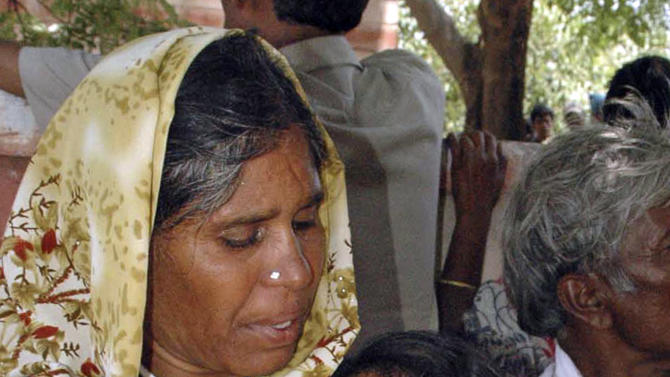 Relatives of victims of a train accident cry outside a government hospital in Penukonda, about 170 kilometers (105 miles) north of Bangalore, India, Tuesday, May 22, 2012. A passenger train rammed into a parked freight train and burst into flames before dawn Tuesday, killing more than a dozen people in southern India, officials said. (AP Photo)
