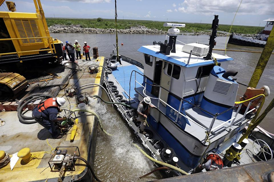"Workers pump out water after raising ""C-Pec,"" the 47 foot tugboat which sank Saturday in the middle of the Mississippi River, near Venice, La., Wednesday, July 10, 2013. (AP Photo/Gerald Herbert)"