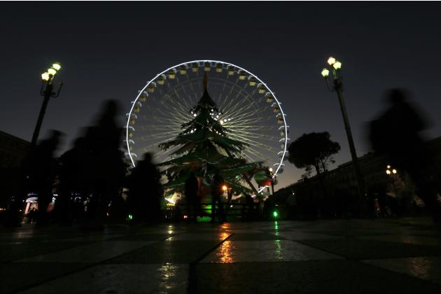 People walk past a giant Christmas tree near a Ferris wheel on the place Massena as part of Christmas holiday season illuminations in Nice