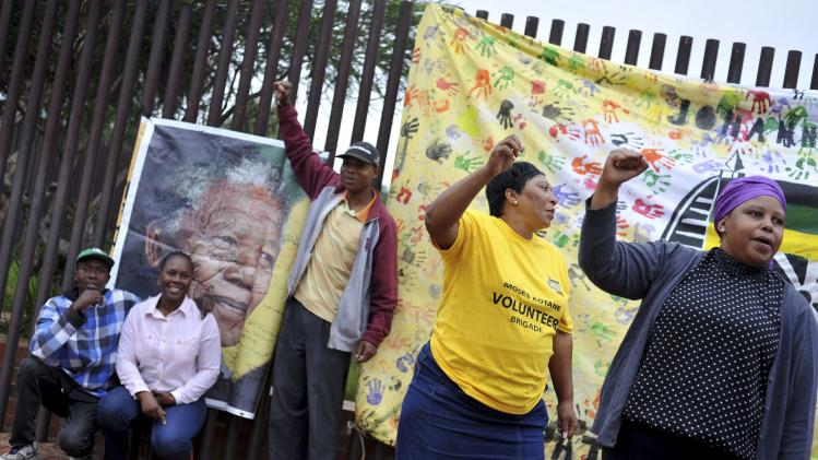 People gather on Vilakazi Street in Soweto, where former South African President Nelson Mandela resided when he lived in the township