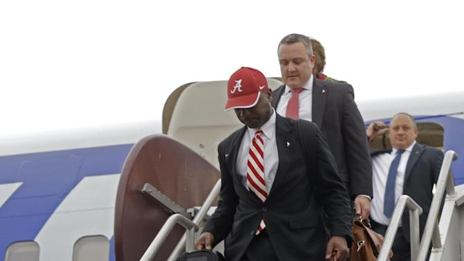 Alabama coach Nick Saban, front, arrives with his team at Louis Armstrong International Airport in Kenner, La., Saturday, Dec. 27, 2014. Alabama plays Ohio State in the Sugar Bowl NCAA college football playoff semifinal on New Year's Day, (AP Photo/Gerald Herbert)