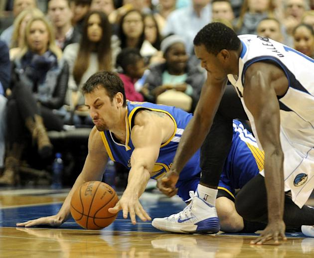 Golden State Warriors center Andrew Bogut, left, and Dallas Mavericks center Samuel Dalembert go after a loose ball in the first half during an NBA basketball game on Wednesday, Nov. 27, 2013, in Dall
