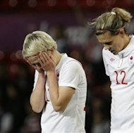 Canada&#39;s Sophie Schmidt, left, and her teammate Canada&#39;s Christine Sinclair, right, react after their team lost during their semifinal women&#39;s soccer match between the USA and Canada at the 2012 London Summer Olympics, in Manchester, England, Monday, Aug. 6, 2012. (AP Photo/Hussein Malla)