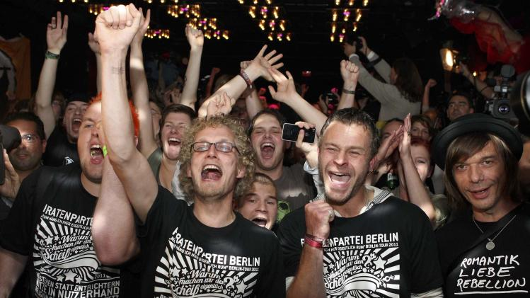 Supporters of the Pirate Party celebrate after the first exit polls have been published after the Berlin state elections in Berlin Sundey, Sept. 18, 2011. Preliminary results show that voters in Berlin have returned the center-left Social Democratic mayor to his seat, while the technology-friendly Pirate Party has made its debut in a German legislature. (AP Photo/dapd, Adam Berry)