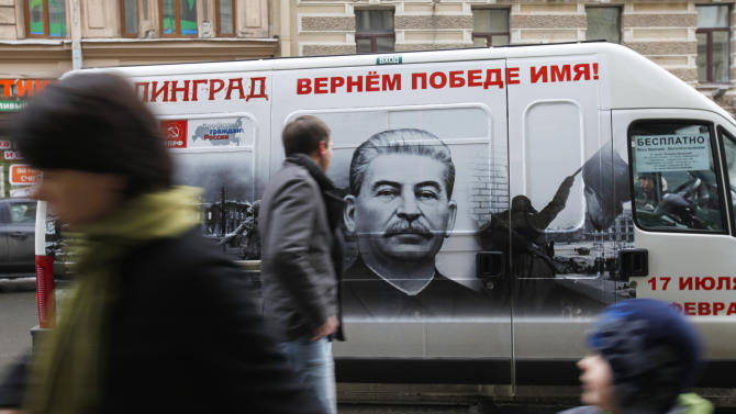 """FILE - In this Saturday, Feb. 2, 2013 file photo people walk by a bus adorned with a portrait of Soviet dictator Josef Stalin and a sign reading """"Stalingrad gets back its victorious name""""  in St. Petersburg, Russia. An opinion survey commissioned by the Carnegie Endowment has revealed that Soviet dictator Josef Stalin has remained widely admired in Russia and other ex-Soviet nations despite his repressions that killed millions of people. It has found that support for Stalin in Russia has actually increased since the 1991 collapse of the Soviet Union.(AP Photo/Elena Ignatyeva)"""