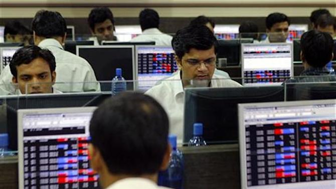 Brokers trade on their computer terminals at stock brokerage firm in Mumbai