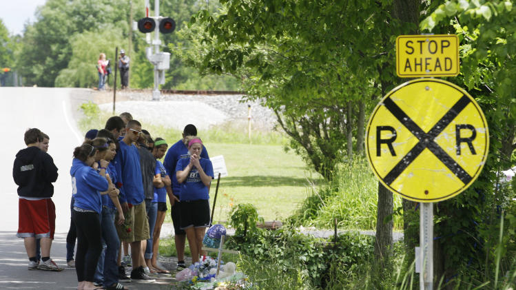 Brunswick High School students console each other at a car crash site Monday, June 4, 2012, near Brunswick, Ohio. A fourth victim of the crash, Kevin Fox, died Monday, a day after he was thrown from a car just hours before his high school graduation in a northeast Ohio crash that killed three other teens. A car carrying Fox and four other teenagers went airborne, crashed, and flipped onto its roof at a railroad crossing early Sunday. (AP Photo/Tony Dejak)