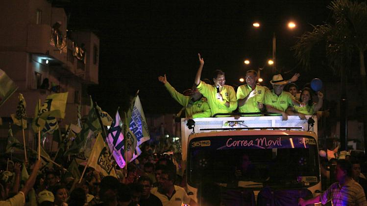 Ecuador's President and candidate for re-election Rafael Correa and vice presidential candidate Jorge Glass campaign atop a vehicle during a rally in Guayaquil, Ecuador, Wednesday, Feb. 13, 2013. Presidential elections in Ecuador are scheduled for Feb. 17. (AP Photo/Dolores Ochoa)