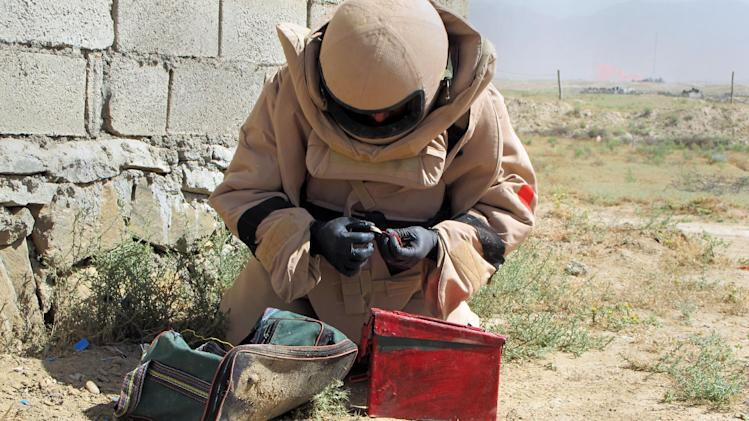 In this Tuesday, June 11, 2013 photo, Hayatullah inspecting cables of a defused IED (improvised explosive device) in a bag during an defusing training exercise on the outskirts of Kabul, Afghanistan. A few years ago, there were almost no Afghan bomb disposal experts. Now, there are 369 _ and the international coalition is rushing to train hundreds more before the exit of most coalition forces by the end of next year. (AP Photo/Kay Johnson)