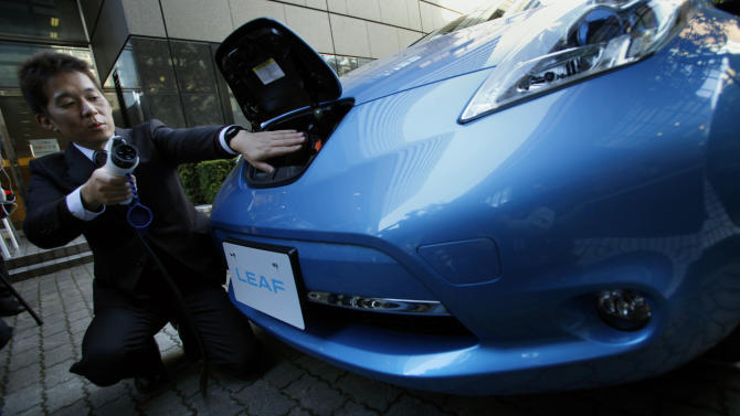 Nissan Motor Co. employee Kazuhiro Fujibayashi demonstrates the electric recharge plug-in process of the company's latest LEAF car for photographers  in Tokyo, Tuesday, Nov. 20, 2012. The upgraded Leaf electric car from Nissan can travel further without recharging, comes in a cheaper model and tells drivers how much battery life is left.(AP Photo/Junji Kurokawa)